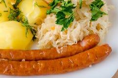 烤香肠用蒸的圆白菜德国泡菜和煮的土豆 免版税图库摄影
