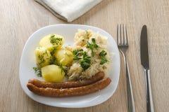 烤香肠用蒸的圆白菜德国泡菜和煮的土豆 免版税库存照片
