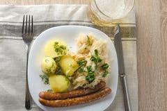 烤香肠用蒸的圆白菜德国泡菜和煮的土豆 库存图片