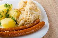 烤香肠用蒸的圆白菜德国泡菜和煮的土豆 库存照片