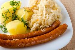 烤香肠用蒸的圆白菜 图库摄影