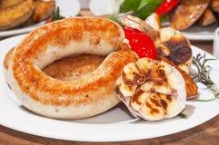 烤香肠用被烘烤的土豆、西红柿和草本 免版税库存照片