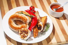 烤香肠用被烘烤的土豆、西红柿和草本 库存图片