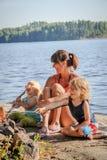 烤香肠的母亲和两个儿子 免版税库存图片