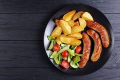 烤香肠,被烘烤的土豆,菜沙拉 免版税图库摄影