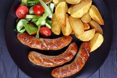 烤香肠,被烘烤的土豆,菜沙拉 免版税库存图片