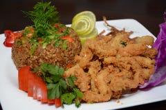 烤鱼和米用开胃菜在白色板材 免版税库存图片