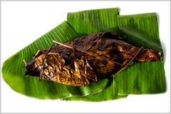 烤鱼在香蕉叶子包裹的镀金面领袖鲂隔绝在白色背景 Sparus aurata 免版税图库摄影