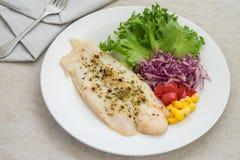 烤鱼片牛排用草本和菜在板材 免版税库存图片