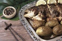 烤鱼用土豆和在一个银盘的柠檬切片用亚洲木棍子和香料在一张木桌上 库存图片