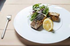 烤鱼用柠檬和沙拉 免版税库存图片