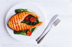 烤鲑鱼排用蕃茄樱桃和菠菜 图库摄影