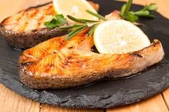 烤鳟鱼内圆角装饰在黑板岩的柠檬 库存照片