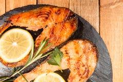 烤鳟鱼内圆角装饰在黑板岩的柠檬 免版税库存图片