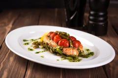 烤鳟鱼用蕃茄豆科的豆和柠檬在白色板材木背景 顶视图 库存照片