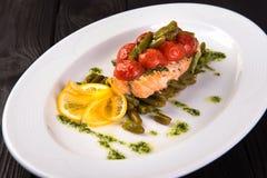 烤鳟鱼用蕃茄豆科的豆和柠檬在白色板材 关闭 免版税库存照片