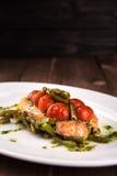 烤鳟鱼用蕃茄豆科的豆和柠檬在白色板材 顶视图木后面地面 免版税库存照片