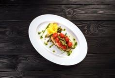 烤鳟鱼用蕃茄豆科的豆和柠檬在白色板材 顶视图 免版税图库摄影