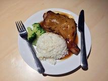 烤鸡烘烤冠上了用调味汁并且煮沸了硬花甘蓝,并且白色烹调了与刀子的在白色盘的米和叉子 库存照片
