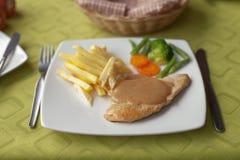 烤鸡用colca调味汁、炸薯条和菜沙拉 免版税库存图片