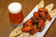 烤鸡翼和杯啤酒 免版税库存图片