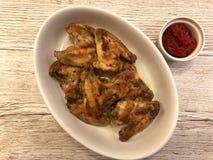 烤鸡翼用荷兰芹和调味汁在板材 免版税库存图片