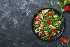 烤鸡肉沙拉用新鲜的草莓和辣芝麻菜,黑暗的厨房用桌背景,顶视图 库存照片