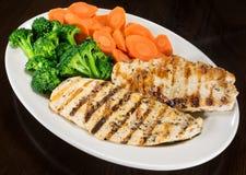 烤鸡胸脯、硬花甘蓝和红萝卜在板材 库存图片
