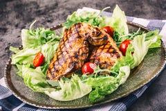 烤鸡胸脯用不同的变异用莴苣沙拉西红柿蘑菇草本切了在一个木板的柠檬或 免版税库存图片