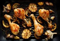 ?? 烤鸡腿、鼓槌与加法,大蒜、柠檬和迷迭香在格栅板材,顶视图 图库摄影