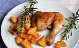 烤鸡腿用油煎的土豆 免版税库存照片