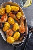 烤鸡腿用煮沸的土豆和菜在黑背景 复制空间 顶视图 库存图片