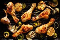 烤鸡腿用芳香草本和菜在烤肉板材 免版税库存图片