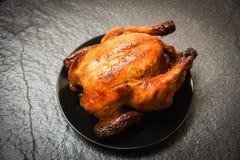 烤鸡-在黑色的盘子和黑暗的背景烤的被烘烤的整鸡在顶视图 库存图片