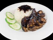 烤鸡teriyaki用米和菜在一块白色板材在黑背景与裁减路线 图库摄影