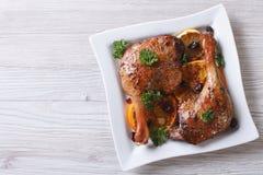 烤鸭子腿有桔子和葡萄干顶视图,水平 免版税库存照片