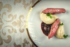 烤鸭胸脯用红色调味汁和芹菜纯汁浓汤在白色板材,餐馆的,现代美食术产品摄影服务 库存图片