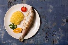 烤整个鳟鱼、土豆、柠檬和大蒜,关闭  与拷贝空间的蓝色背景 免版税库存照片
