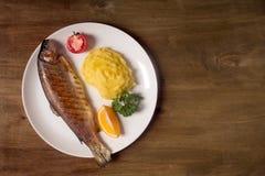 烤整个鳟鱼、土豆、柠檬和大蒜,关闭  木背景 免版税库存照片