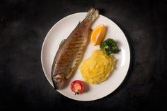 烤整个鳟鱼、土豆、柠檬和大蒜,关闭  免版税库存照片