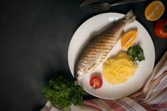 烤整个鳟鱼、土豆、柠檬和大蒜,关闭  库存照片