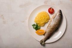 烤整个鳟鱼、土豆、柠檬和大蒜,关闭  免版税库存图片