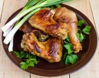 烤水多的鸡(腿,小翅膀)在轻的木背景的黏土板材 免版税库存照片