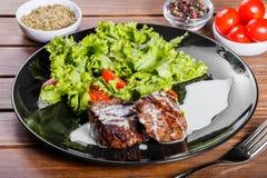 烤beaf牛排肉用新鲜蔬菜沙拉和蕃茄在黑色的盘子,木背景 免版税库存照片