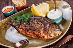 烤dorado在板材的鱼用柠檬和绿色在木背景 免版税库存照片