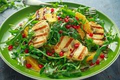 烤Halloumi乳酪沙拉用桔子、火箭叶子、石榴和南瓜籽 健康的食物 库存照片