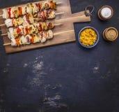 烤kebabs用胡椒,猪肉和菠萝在切板调味汁和调味料毗邻地方文本的 免版税库存图片