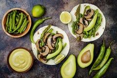 烤portobello,芦笋,甜椒,青豆法加它 Poblano与墨西哥胡椒,香菜,鲕梨crema的蘑菇炸玉米饼 图库摄影