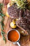 烤ribay牛排顶视图用土豆、菜和调味汁在一块木板材 特写镜头 免版税库存照片