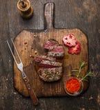 烤ribeye牛排切了†‹在一个切板的†‹有一个叉子、红色调味汁、胡椒和蕃茄的在土气木背景, 免版税库存图片